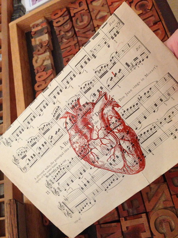 Letterpressed anatomical heart over music sheet printed by Appalachia Press.