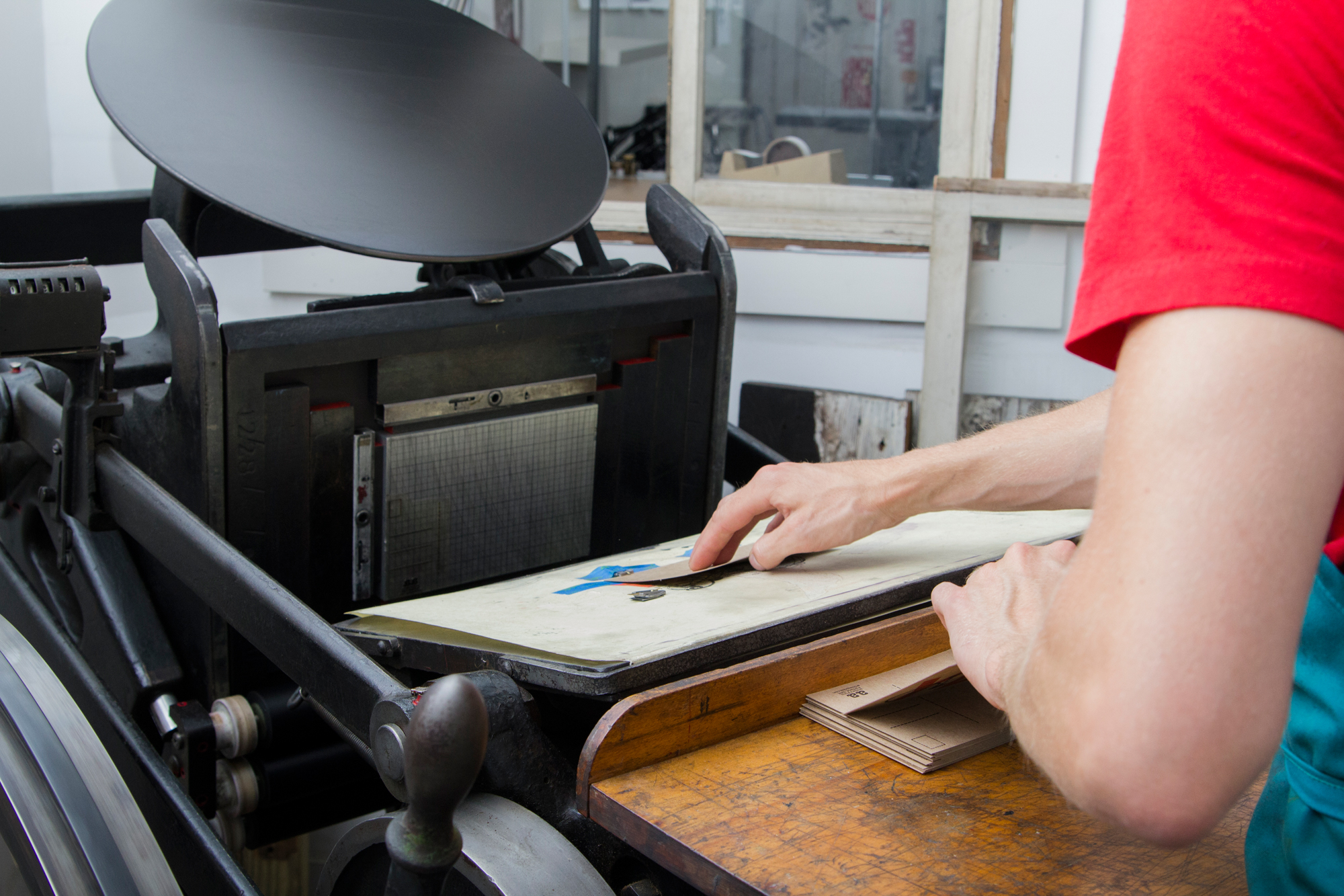 Archie Archambault of Archie's Press sets up a printing job on his Chandle & Price press.